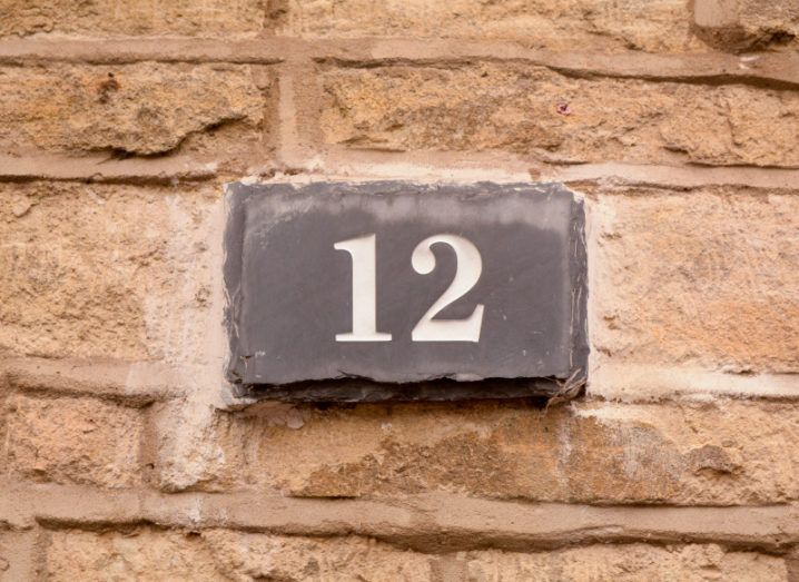 The number 12 written on a stone sign on a brick wall.