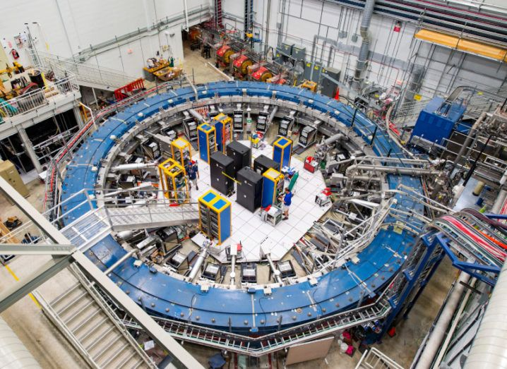 The Muon g-2 ring sits in its detector hall amid electronics racks, the muon beamline, and other equipment.
