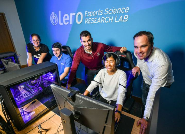 Five people are gathered around gaming computers. The wall behind them says 'Lero Esports Science Research Lab'.