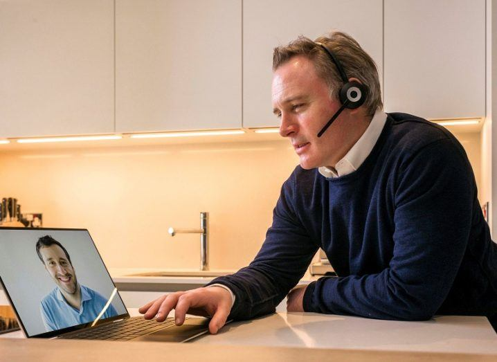 A man wearing a headset talks to a colleague on a video call.