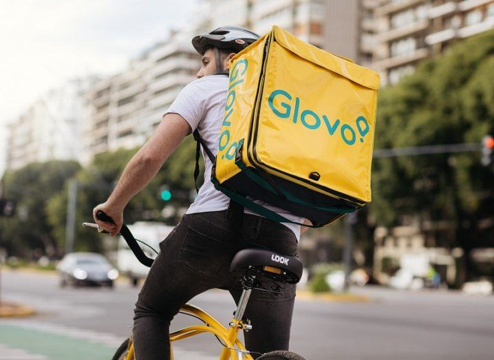 Glovo courier cycling through the street wearing a company-branded backpack.
