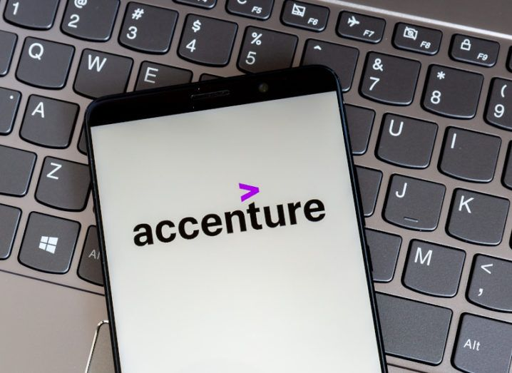 A smartphone sits on a laptop keyboard. The Accenture logo is on the phone screen.