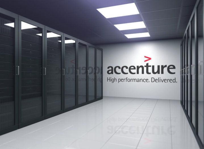 The Accenture logo on a white wall at the back of a computer server room.