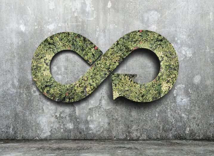 Green circular economy concept with a green infinity symbol against a grey stone wall.