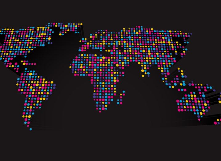 Abstract 3D world map made up of small colourful dots on a black background.