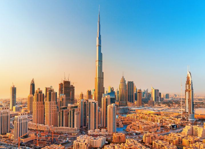 The skyline of downtown Dubai's numerous high-rise buildings against a golden sunset.