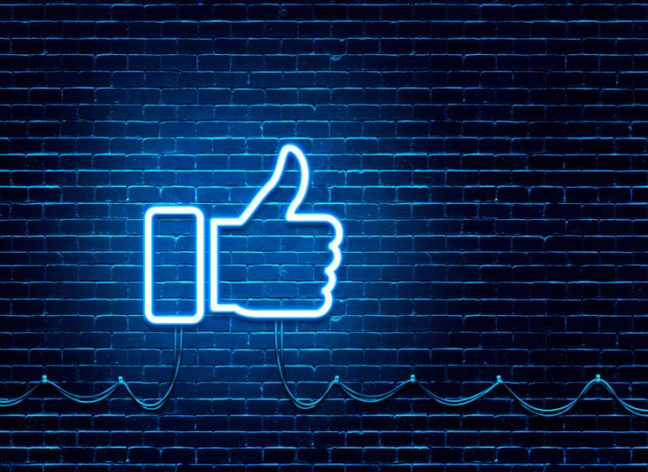 A neon thumbs-up sign, similar to the Facebook 'like' symbol, is glowing against a dark blue wall.