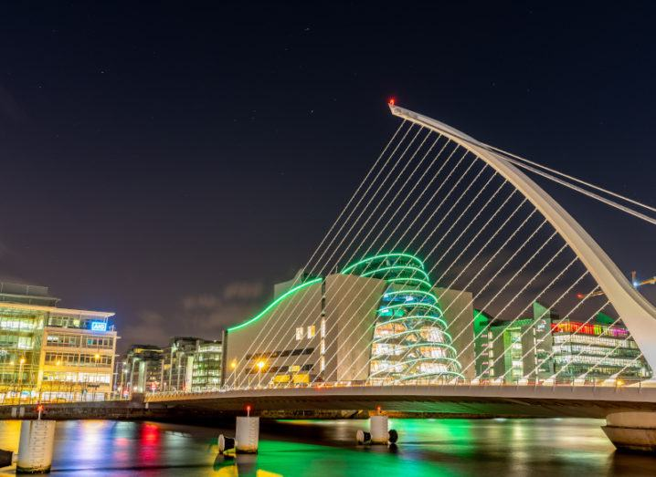 Image of the Samuel Beckett bridge in Dublin at night, with the Convention Centre and offices lit up in the background.