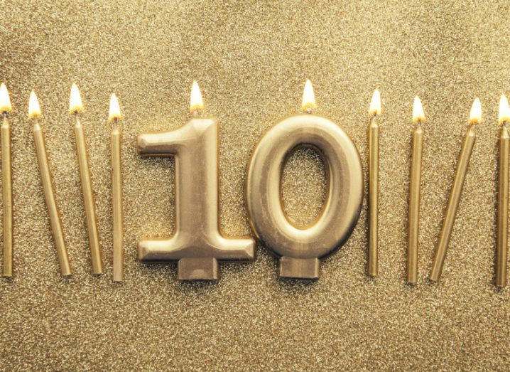 A row of 10 lit golden candles on a glittering background. The candles in the centre are shaped like the number 10.
