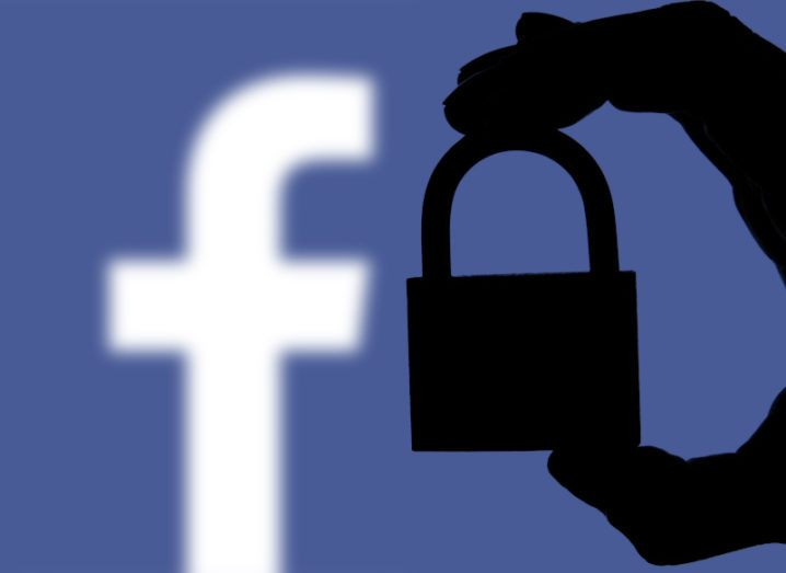 The Facebook logo is behind a silhouette of a hand holding a padlock.