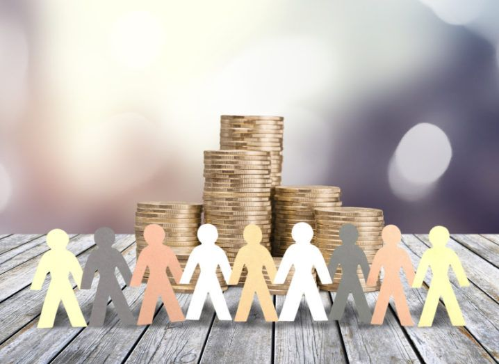 A row of paper figures in different shades standing in front of a stack of coins.