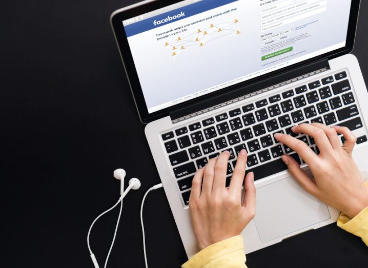 A person's hands are using a laptop, which has the Facebook login page open on the screen.