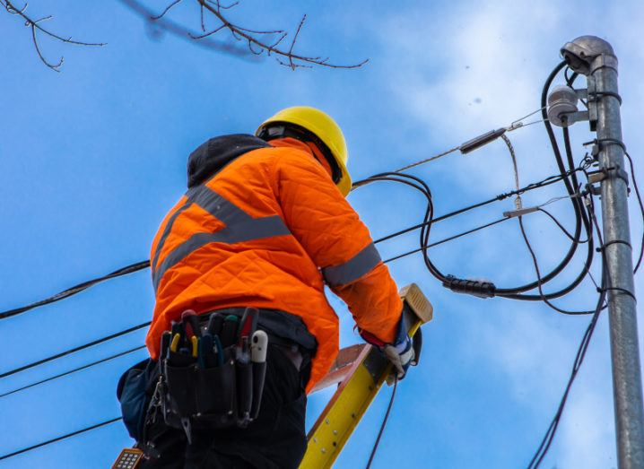 A telecoms operative is seen working from a ladder on a utility pole to install a fibre network, wearing high visibility clothing and a hard hat.