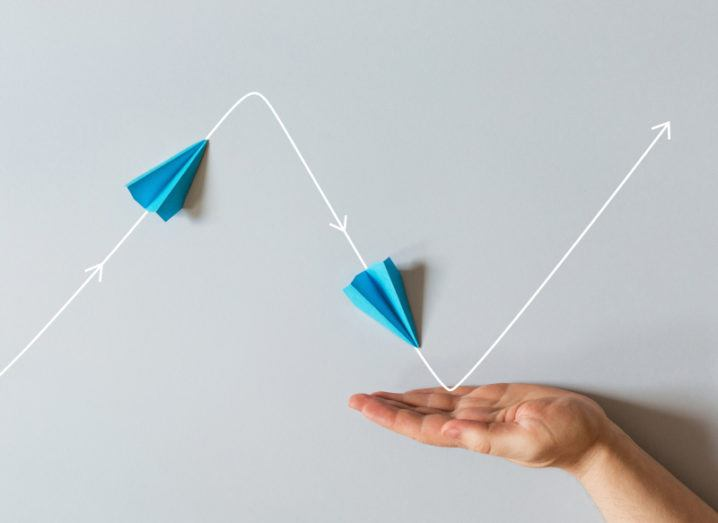 A person's hand is underneath a zigzag graph line, which features a paper airplane going up and down.