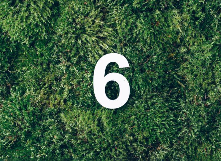 A white number six is placed on top of a grassy ground.