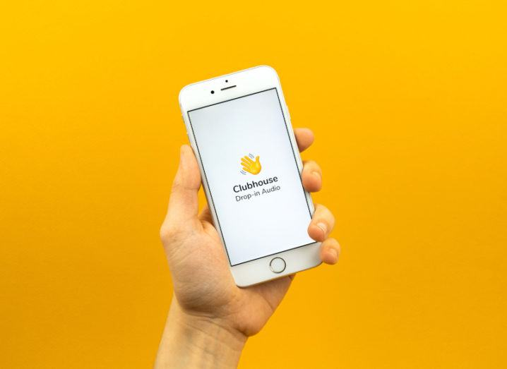 A hand holding a white iPhone displaying the Clubhouse icon with a waving hand emoji.
