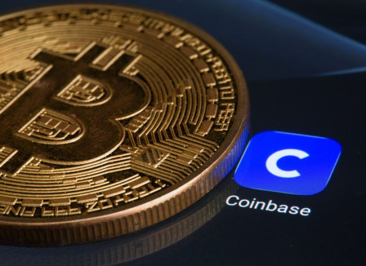 A gold coin bearing the bitcoin symbol on top of a digital display of the Coinbase logo.
