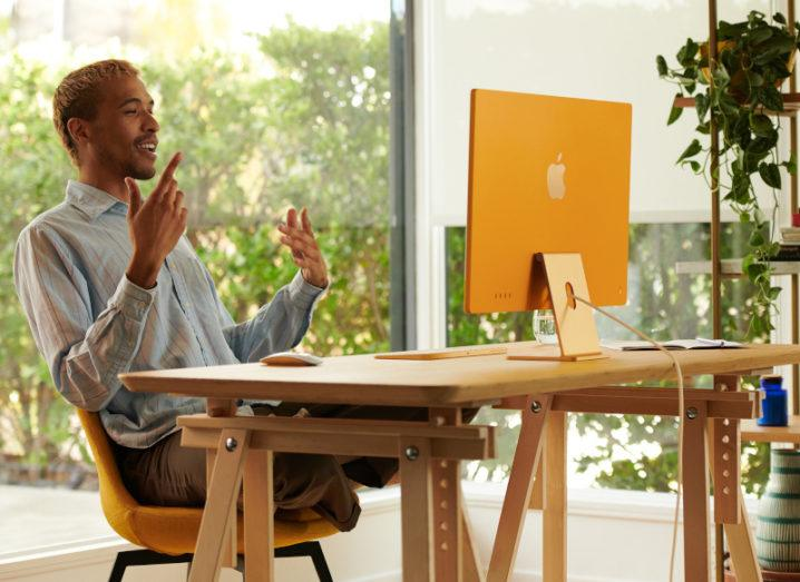 A man sitting at a desk in a brightly lit room while he's working at a new orange Apple iMac.