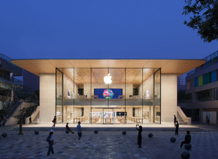 An Apple store brightly lit from the inside in a Beijing square as people mill around at dusk.