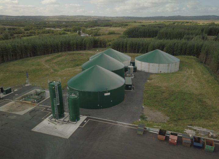 An aerial view of a large green biogas production facility, comprising several green round buildings on a large site.