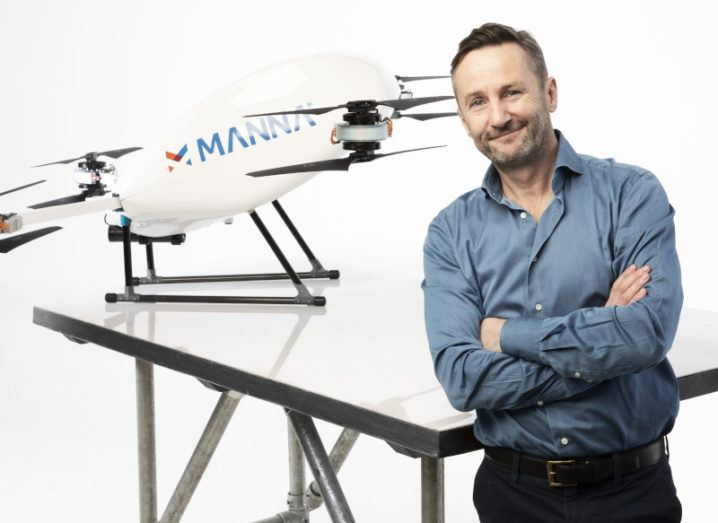 Bobby Healy stands with his arms crossed beside a Manna drone.
