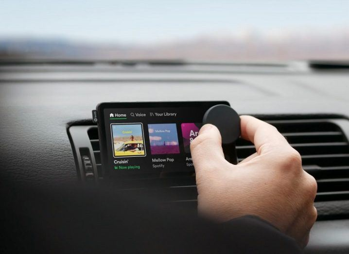 A hand is turning a dial on a small device with a screen that is resting on the dashboard of a car.