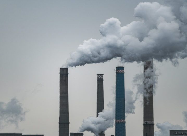 Four industrial chimneys against a dusky grey sky with plumes of smoke coming from them, representing carbon emissions.