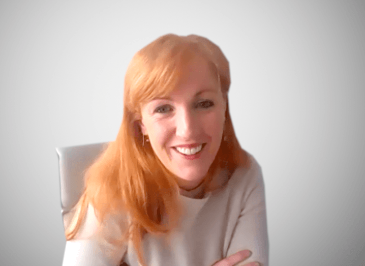 A screen shot of a woman with red hair smiling at the camera on a Zoom call.
