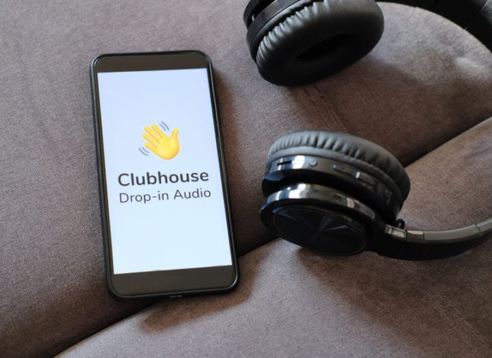 A smartphone sits on a brown couch next to a pair of black headphones. The Clubhouse logo is on the phone's screen.