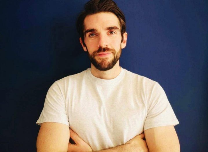 A close-up image of Nori founder Conor Sheridan with his arms folded, standing against a dark wall.
