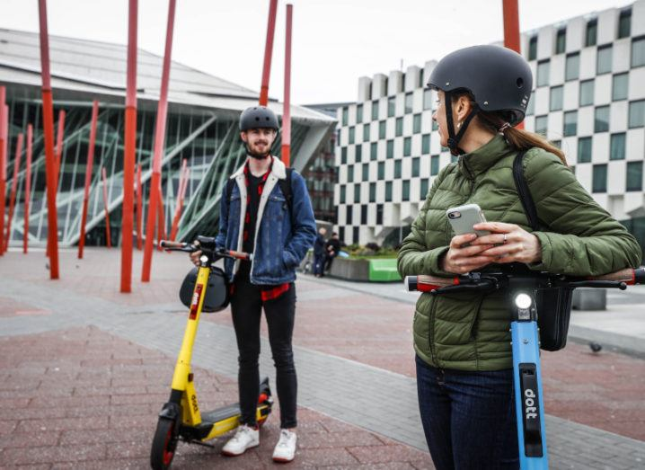 Two people wearing helmets are standing beside Dott e-scooters in Dublin's Grand Canal Dock.