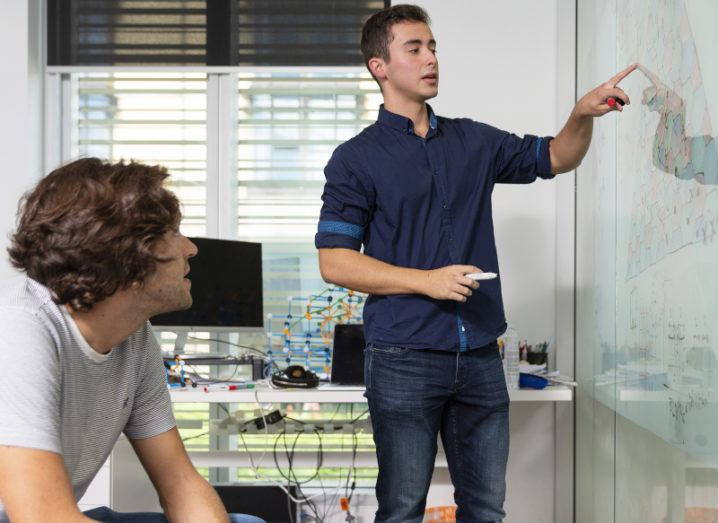 A young man, Pablo Bonilla Ataides, is pointing to a code written out on a whiteboard, while another man sits and watches.