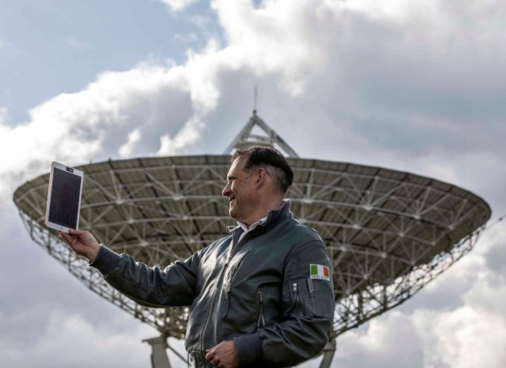 NSC CEO Rory Fitzpatrick holds a tablet outside in front of a large satellite dish. He's wearing a windbreaker jacket with the Irish flag on the arm.