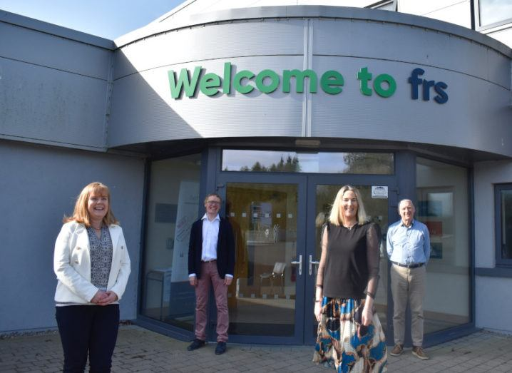 Four people stand outside a building that says 'Welcome to FRS' above the door.