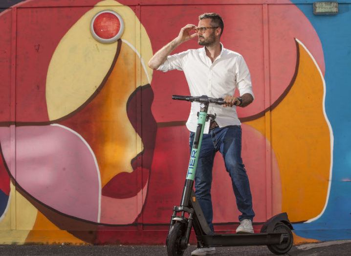 A man is standing with one of Tier's e-scooters in front of a colourfully painted wall.