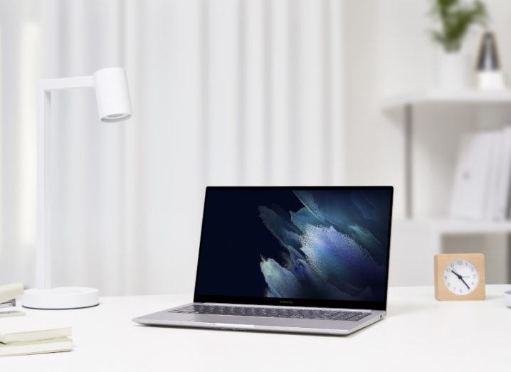 A new Samsung Galaxy Book laptop is sitting on a white desk, beside a lamp and a clock.