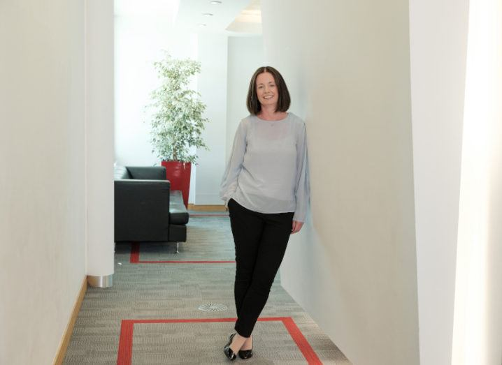 Gillian O'Sullivan leans against a wall in a bright office space.
