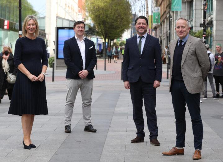 One woman and three men stand apart in a line along a city street in Dublin, smiling at the camera.