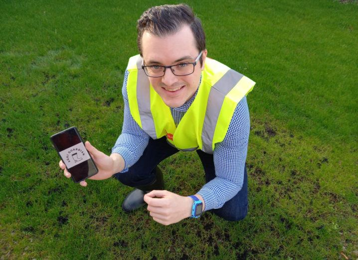 A man in a high-vis vest crouches in a field holding a smartphone. The screen says Agri Guardian.