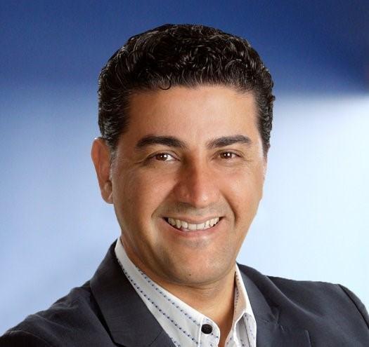 A headshot of Jamshid Rezaei against a blue background.