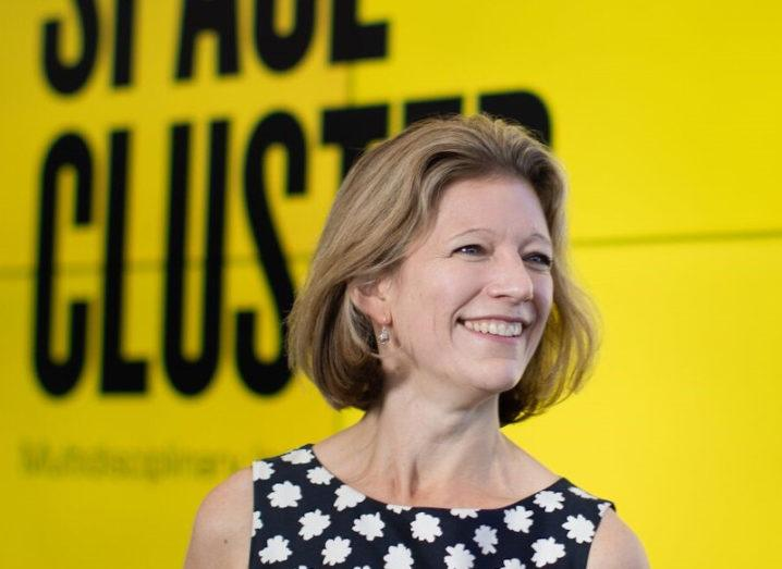 Joanna Hart stands in front of a bright yellow screen that reads 'Harwell Space Cluster'.
