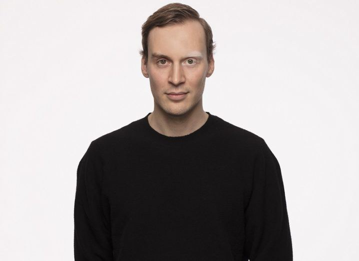 A man in a black sweaters stands against a plain background.