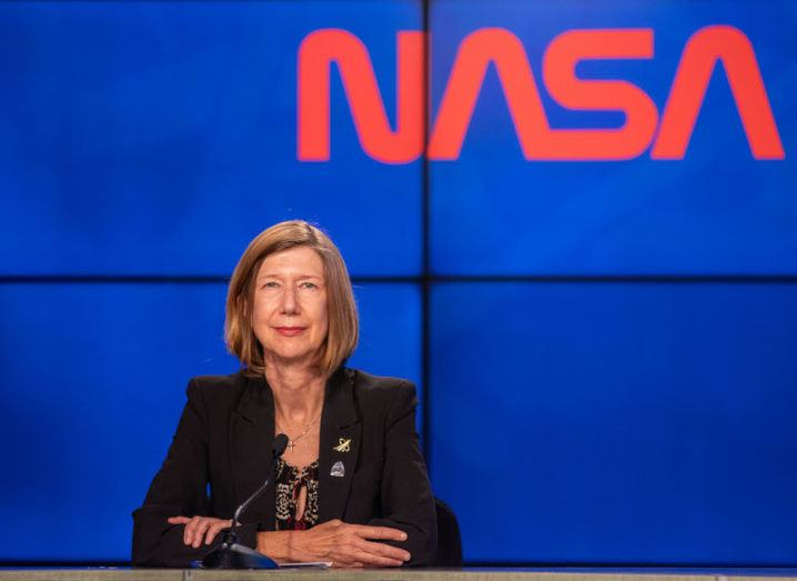 Kathryn Lueders, a woman with short blonde hair wearing a black blazer sits at a desk with the NASA logo written in red on a blue wall behind her.