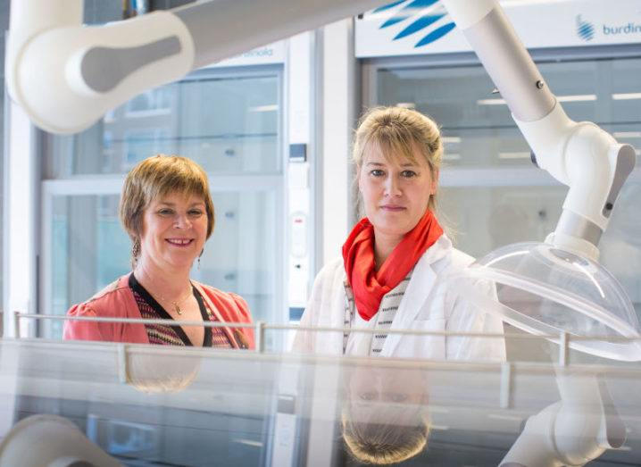 Two women stand beside each other in the white surrounds of a research lab.