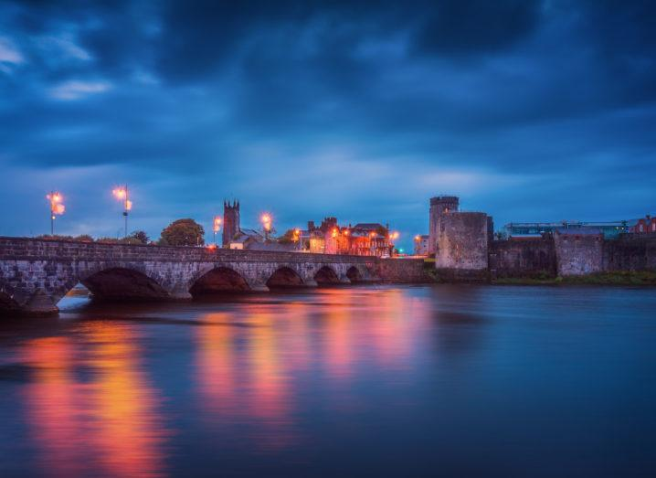 Panoramic view over medieval King John's Castle and River Shannon in Limerick city at night.