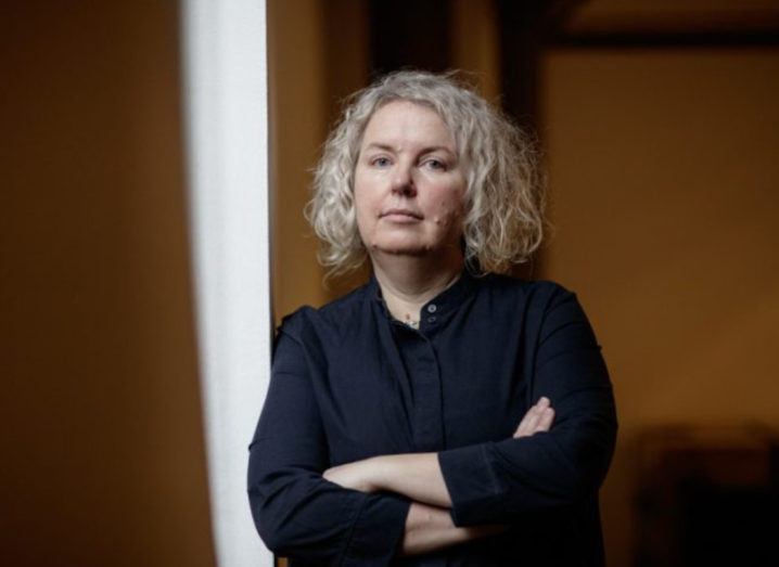 Prof Linda Doyle, the new provost of Trinity College Dublin, is standing with her arms folded while looking into the camera.