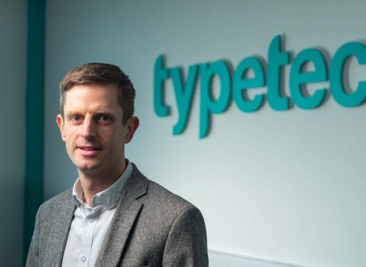 Mark Fitzgerald, COO at Typetec, is standing in front of a wall with company branding.
