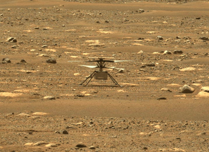 A small drone-like device sitting on a rocky red landscape. It is the Mars helicopter Ingenuity on the surface of Mars.