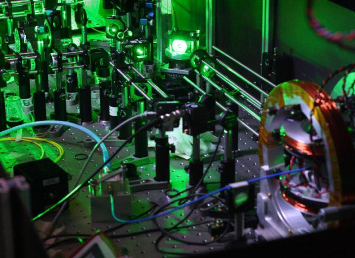 Laboratory equipment is set up under green lighting for quantum physics experiments.