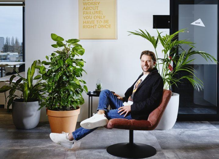 MessageBird's Robert Vis sits in casual clothes in a chair in an office.